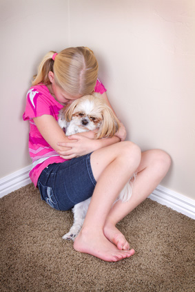 Very sad little girl in pink shirt hugging her sad looking dog